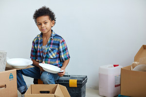 Boy helping parents unpack box with plates