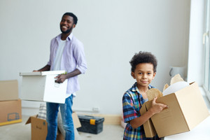 Boy holding box with house supplies while helping his father at home