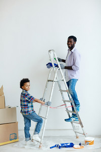 Boy holding ladder while his father painting wall in new flat