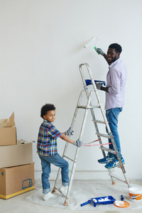 Boy holding ladder while his father standing on it and painting wall