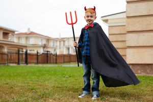 Boy in warlock holding trident and looking at camera while standing on grass by corner of house