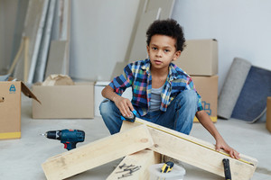 Boy measuring length of wooden plank