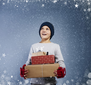 Boy with  christmas present among snow falling