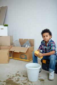 Boy with sponge sitting on tool-box