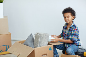 Boy with stack of plates sitting by open box with grey rolled rug and pillow