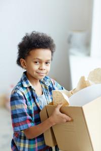 Boy with unpacked box looking at camera