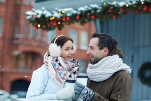 Boyfriend and girlfriend having hot drinks outdoors