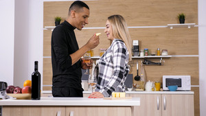 Boyfriend having a cute moment with his gilfriend while cooking. Kitchen fun