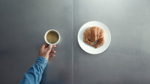 breakfast with coffe and croisant top view how man's hand put on table dish with croissant and cup of coffe