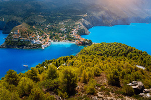 Breathtaking top view to Assos village with local houses. Landmark place of Kefalonia. Lonely white yacht at anchor in calm beautiful lagoon surrounded by pine and cypress trees. Greece