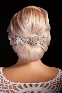 Bridal hairstyle with vintage hair accessories in studio. View from the back. Blond woman.