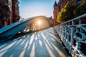 Bridge in the Speicherstadt old warehouse district of Hamburg with sunset evening light. Long shadows in golden hour time