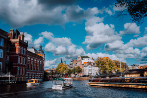 Bright blue sky and fluffy clouds over Amstel in Amsterdam Netherlands, landmark old european city spring autumn landscape