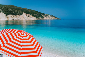 Bright red striped sun beach umbrella on beach against turquoise blue shallow sea water, white limestone coastline and sky in background