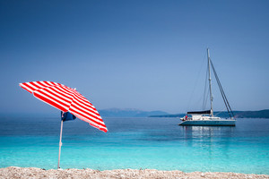 Bright red striped sun beach umbrella on pebble beach against turquoise blue shellow sea water and clean blue sky. White catamaran sailing boat drift in calm blue sea water surface