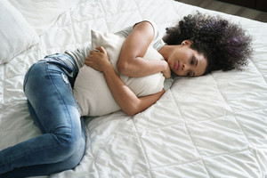 Broken heart young latina woman sitting in bedroom. Depressed hispanic girl at home, lying on bed and holding pillow with sad expression.