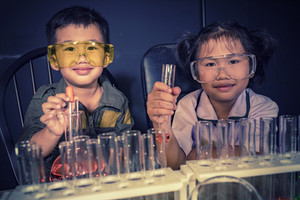 brother and sister studying in school science research laboratory