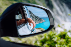 Brown female hand in the car side view mirror. Blue mediterranean sea and white rocks in background