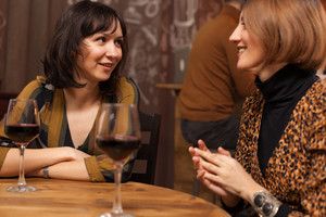 Brunette and blonde hippie young women chatting in a hipster pub. Cheerful young women.