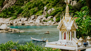 Buddhist spirit house shrine stands on Tanote Bay with Beautiffull Coral Reef, Koh Tao, Thailand