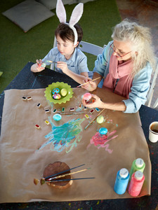 Bunny boy and his grandmother painting Easter eggs