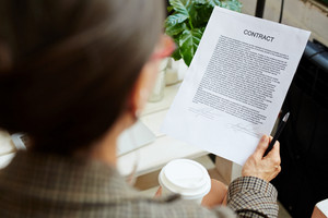 Business contract held and read by businesswoman