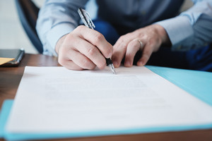 Business man at work in corporate office. Detail of hands of a busy manager signing documents and papers in a blue folder. Copy space.