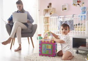 Business mother working at home with child