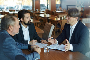 Business partners discussing terms and conditions before signing contract while having formal meeting in spacious restaurant, waist-up portrait