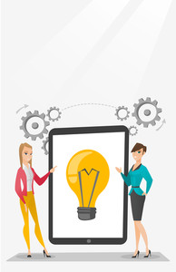 Business partners working on business idea. Caucasian business women discussing business ideas. Businesswomen pointing at idea bulb on tablet screen. Vector flat design illustration. Vertical layout.