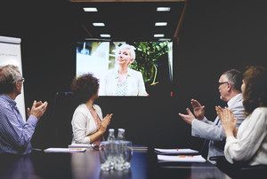 Business people clapping for colleague on video call