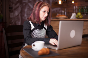 Business person typing on a notebook while serving a coffee in beautiful vintage coffee shop