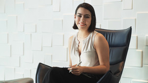 Business woman with tablet computer at work in office waiting room. Successful hispanic female manager sitting on armchair and smiling with confident expression
