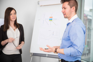 Businessman Giving Presentation While Colleague Looking At Him