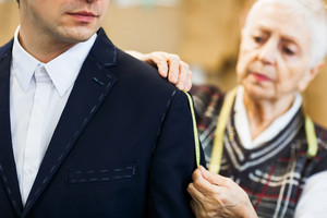 Businessman having his jacket sleeve measured