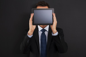Businessman holding digital tablet front of his face