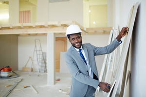 Businessman in hardhat measuring wall panel