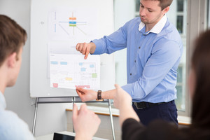 Businessman Showing Chart To Colleagues In Office