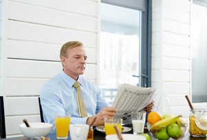 Businessman sitting by table with organic food and reading news