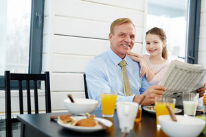 Businessman with newspaper and his daughter sitting by table in the kitchen