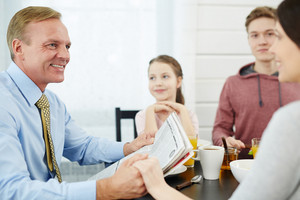 Businessman with newspaper looking at his wife by breakfast on background of son and daughter