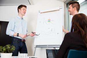 Businessmen Standing By Presentation Board In Office