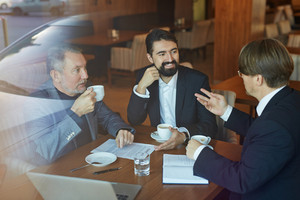 Businessmen talking by cup of coffee at break