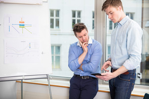 Businessmen Using Tablet Computer While Leaning On Window Sill