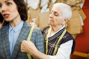 Businesswoman calling while tailor taking measures of her jacket