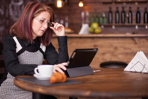 Businesswoman holding her glasses while looking at tablet. Adult antrepreneur woking on vintage coffee shop