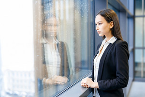 Businesswoman in formalwear looking through office window on rainy day