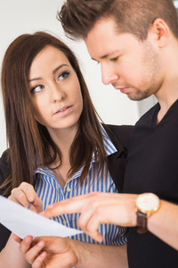 Businesswoman Looking At Male Colleague Reading Document