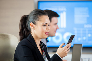 Businesswoman looking at phone in conferece room while a TV is displaying info in the background