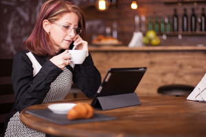 Businesswoman looking at tablet while talking having a conversation on her phone. Working in vintage coffee shop
